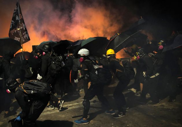 Students use umbrellas as a shields during a clash with police at the Chinese University in Hong Kong,...