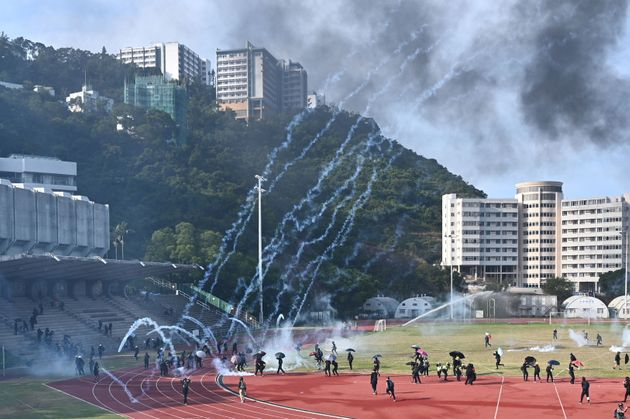 Protesters react after police fired tear gas at the Chinese University of Hong Kong (CUHK), in Hong Kong...