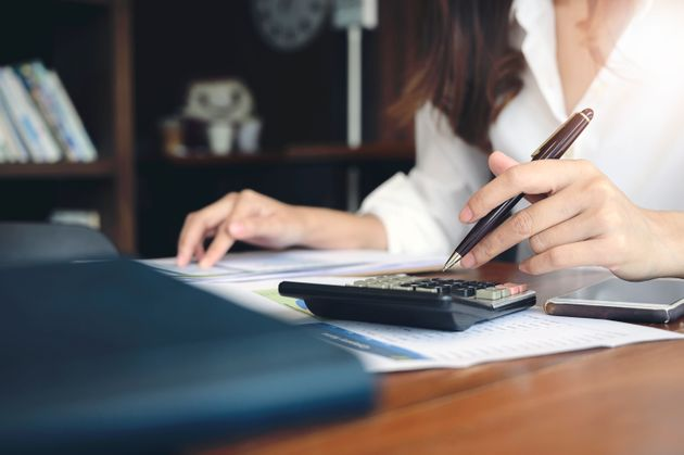Woman using calculator with doing finance at home office. Closeup