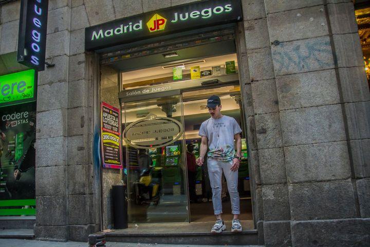 Un joven fuma delante de una casa de apuestas, en Madrid.