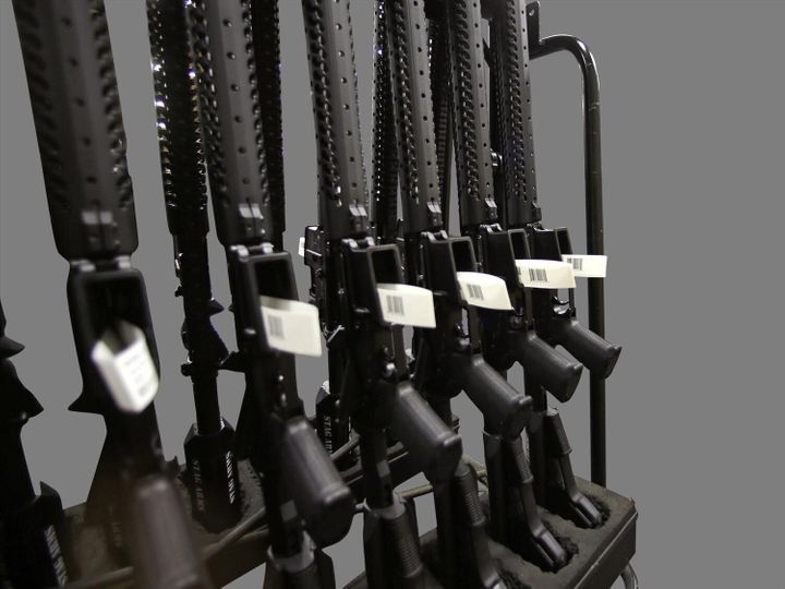 A rack of AR-15 rifles, graphic element on gray