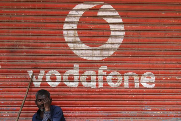 A man sits outside the downed shutters of a shop painted with a logo of Vodafone on its shutter in Mumbai,...