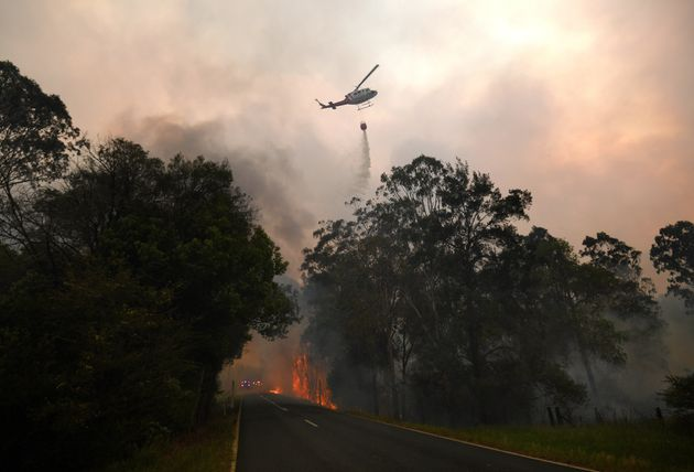 A water bomber drops its load on a bushfire in Nana Glen, near Coffs Harbour, Australia on