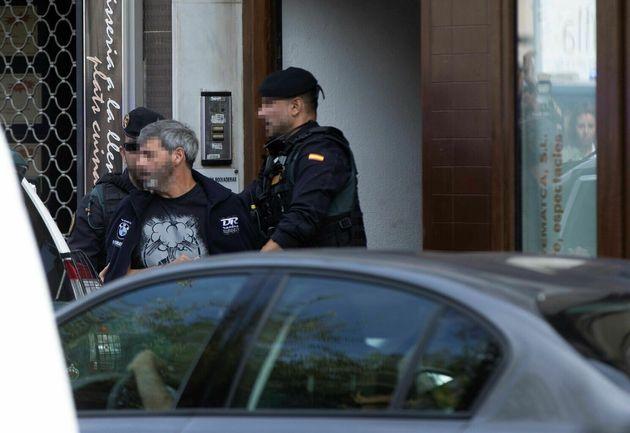 Agentes de la Guardia Civil acompañan a uno de los detenidos durante el registro de un domicilio en