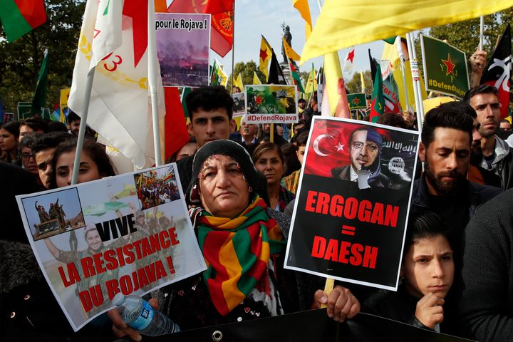 """Protesters carrying a sign reading """"Erdogan=IS"""" referring to Turkish President Recep Tayyip Erdogan take part of a demonstrat"""