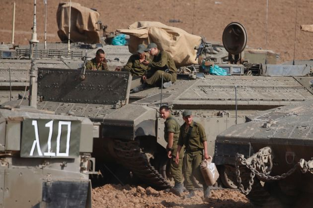 Israeli soldiers prepare their armored vehicles at a gathering point near the border with Gaza on the...