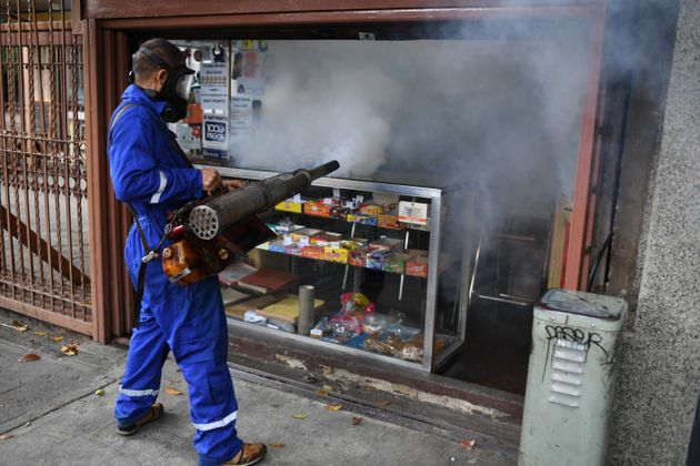 A municipal worker fumigates a store against the aedes aegypti mosquito, vector of dengue fever, Zika...
