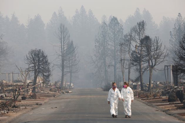 Forensic anthropologists Kyra Stull (L) and Tatiana Vlemincq walk through a trailer park destroyed by...