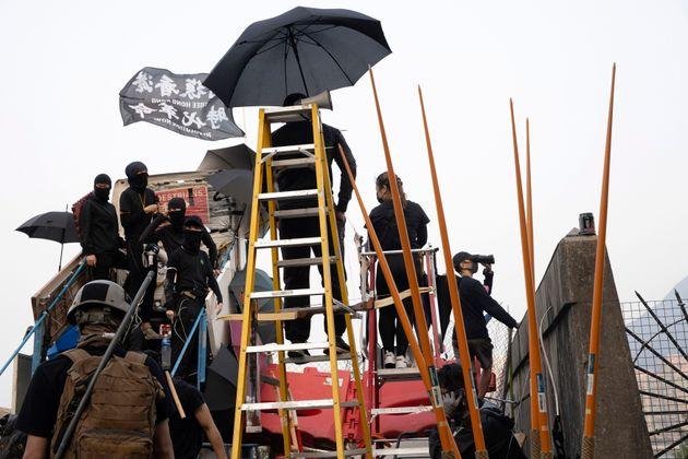 13일 시위대들이 중문대학교로 진입하는 다리 근처에 바리케이드를 쌓고 벽 건너를 살피고