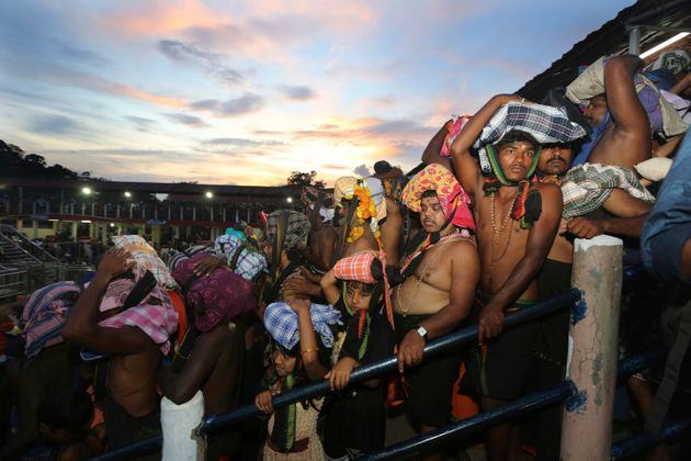 Devotees carrying customary offerings on their heads, wait to worship at the Sabarimala temple in Kerala,...