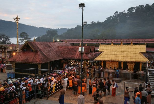 Devotees wait in queues inside the premises of the Sabarimala temple in Pathanamthitta district in Kerala,...