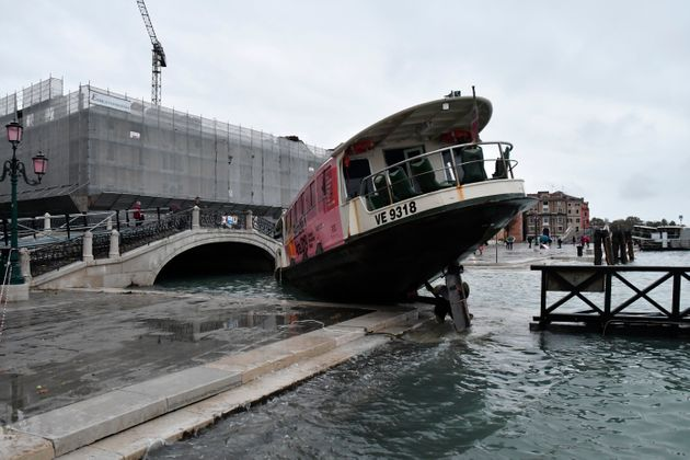 A stranded ferry boat lies on its side, in Venice, Wednesday, Nov. 13, 2019. The mayor of Venice is blaming...