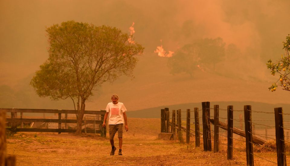 A man walks on a farm as flames approach near the town of Taree, 215 miles north of Sydney, on 14