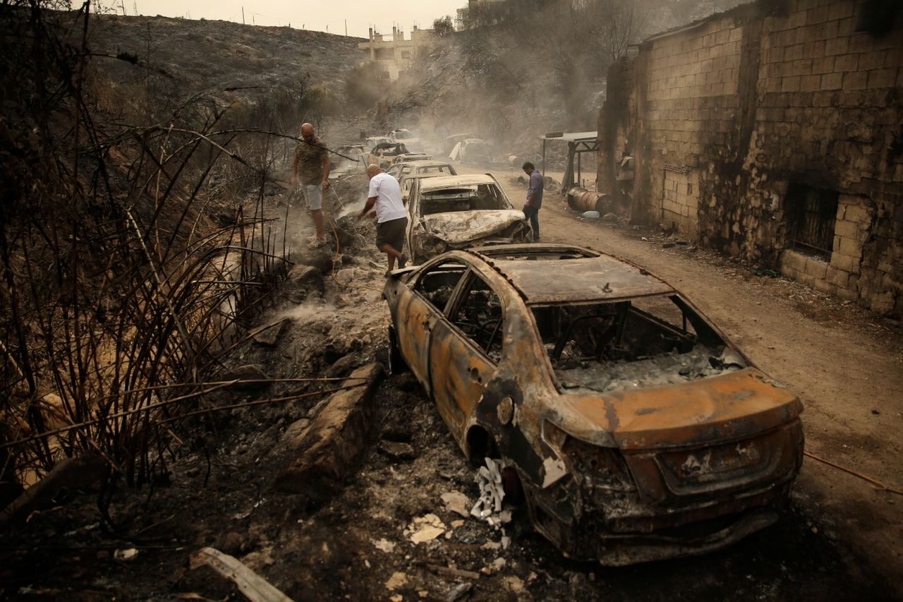 People inspect the remains of cars and shops that were burned in a wildfire in the town of Damour just over 9 miles south of Beirut, Lebanon, on Oct. 15. Strong fires spread in different parts of Lebanon, forcing some residents to flee their homes in the middle of the night as the flames reached residential areas in villages south of Beirut.