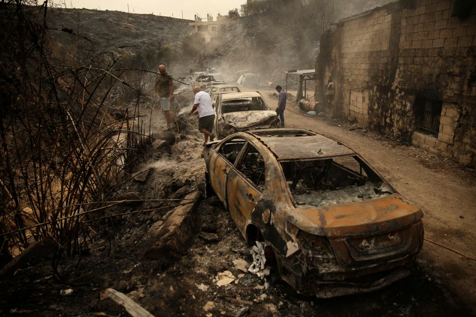 People inspect the remains of cars and shops that were burned in a wildfire in the town of Damour just over 9 miles south of