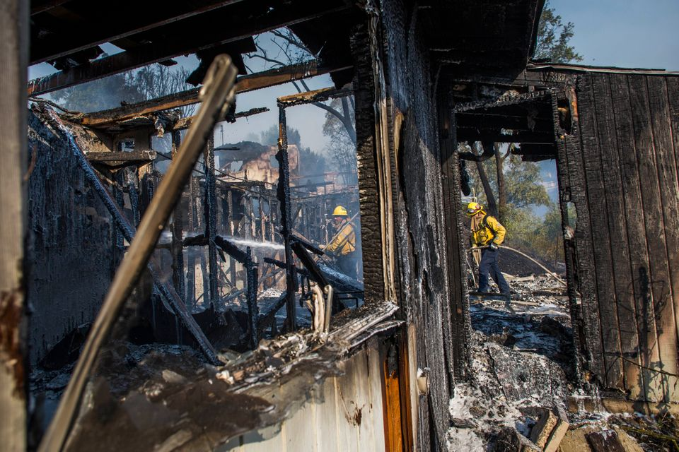 Firefighters battle the Getty Fire in houses in Brentwood, California, on 28 October. The wildfire forced...