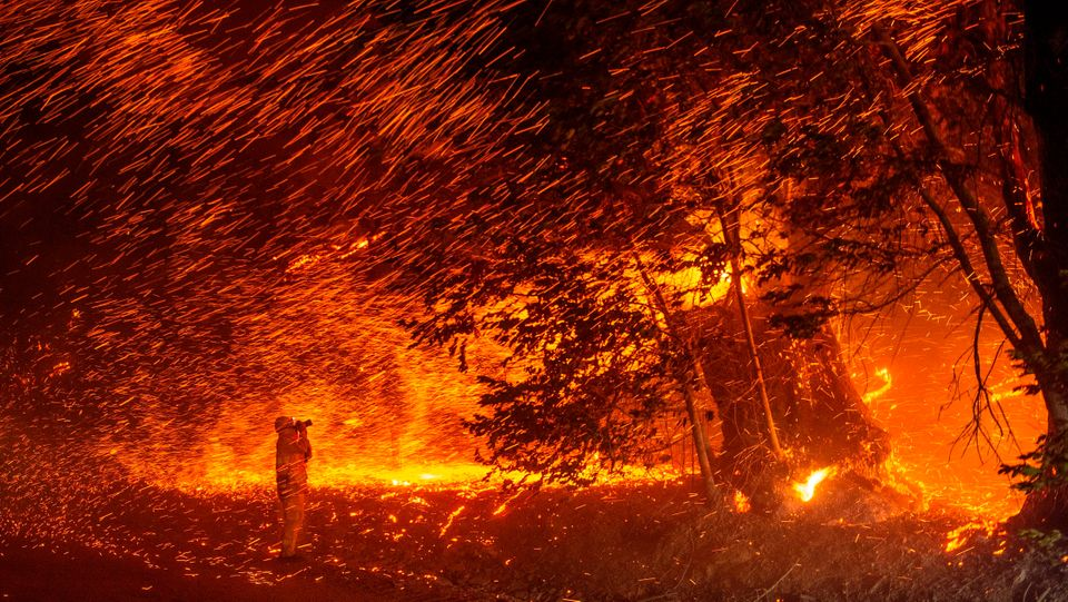 A photographer takes photos amid a shower of embers as wind and flames rip through the area during the...