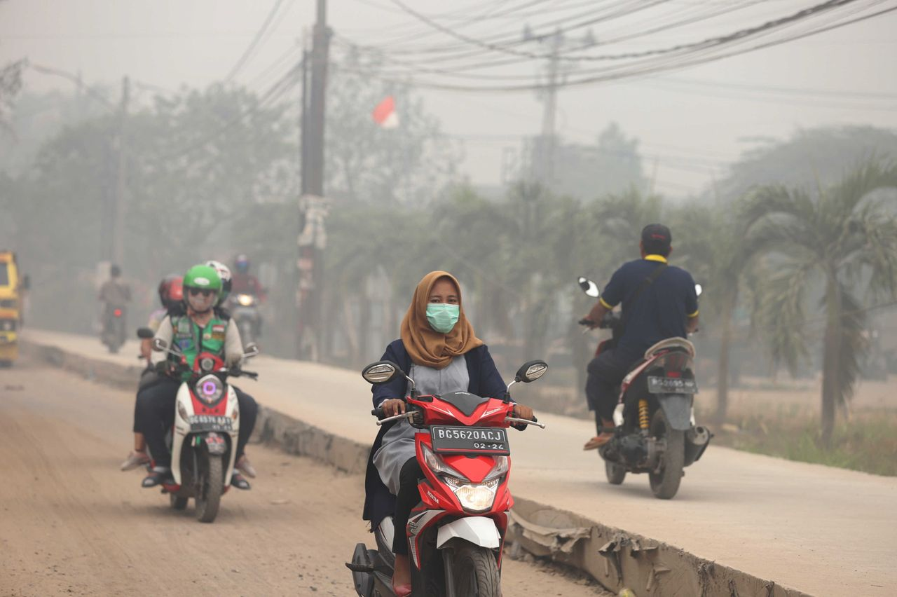 Motorcyclists ride on a road as haze from wildfires blankets the city in Palembang, Indonesia, on Oct. 14. According to the Indonesian Meteorology, Climatology and Geophysics agency, air quality has dropped to dangerous levels.