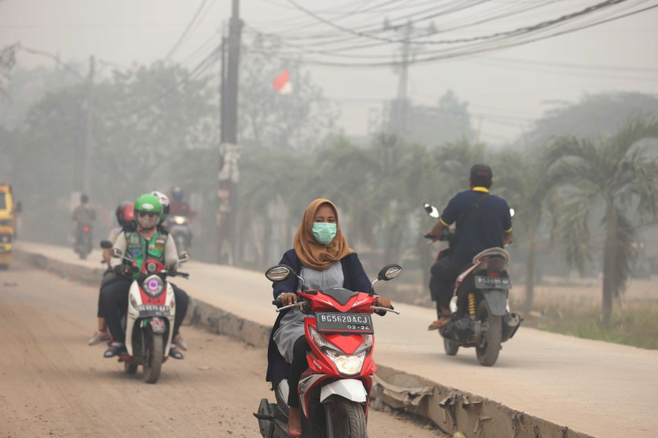 Motorcyclists ride on a road as haze from wildfires blankets the city in Palembang, Indonesia, on 14...