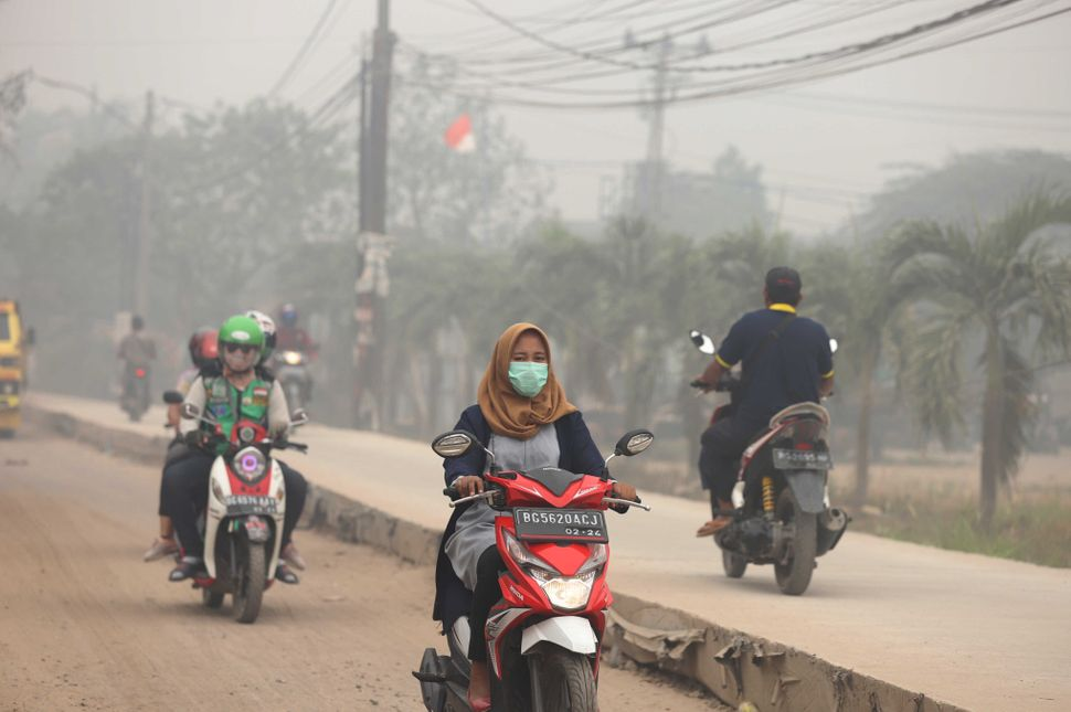 Motorcyclists ride on a road as haze from wildfires blankets the city in Palembang, Indonesia, on Oct. 14. According to the I