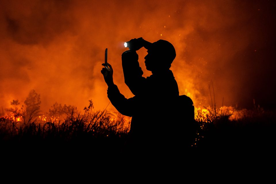 A photographer takes photos of peatland fires in Pekanbaru on 6 October in Riau Province, Indonesia....