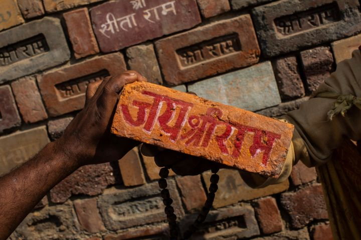 """A man holds a brick reading """"Jai Shree Ram"""" as bricks of the old Babri mosque are piled up in Ayodhya. Nov. 25, 2018."""