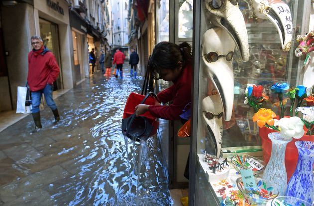 A woman pours out water from a shop onto a flooded walkway during a period of seasonal high water in...