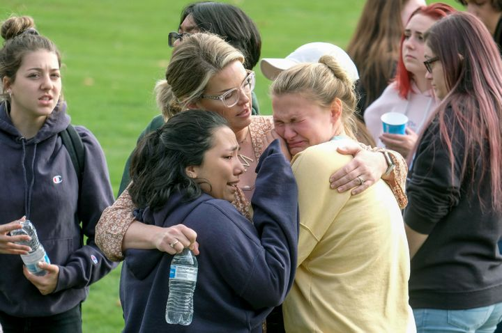 Students are comforted as they wait to be reunited with their parents following the shooting at Saugus High School.
