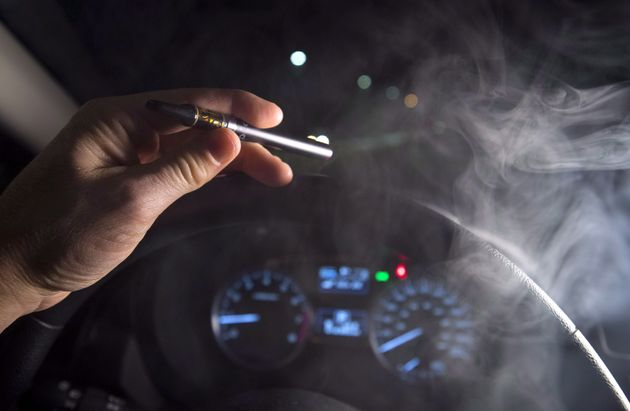 In this photo illustration, vapor from a cannabis oil vaporizer is seen from a driver behind the wheel...