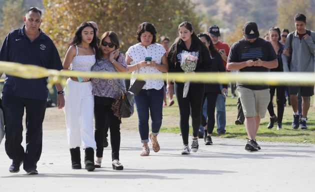 Students and family members walk after being reunited at a park near Saugus High School after a shooting...