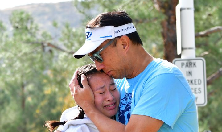 A man embraces his daughter after picking her up at Central Park, after a shooting at Saugus High School.