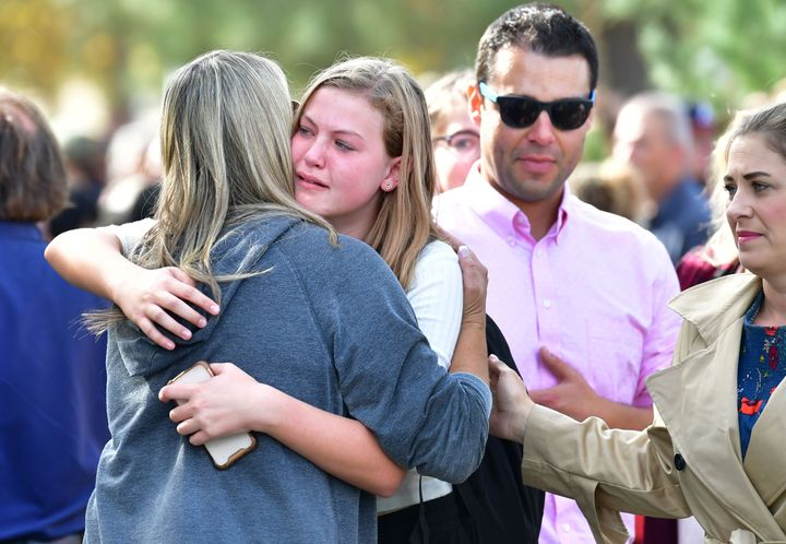 Students and parents embrace after being picked up at Central Park, after a shooting at Saugus High School.