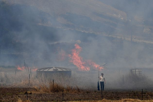 A resident fights a grass fire in the Hillville area near