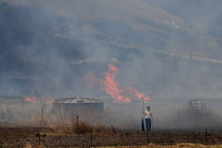 A resident fights a grass fire in the Hillville area near Taree.