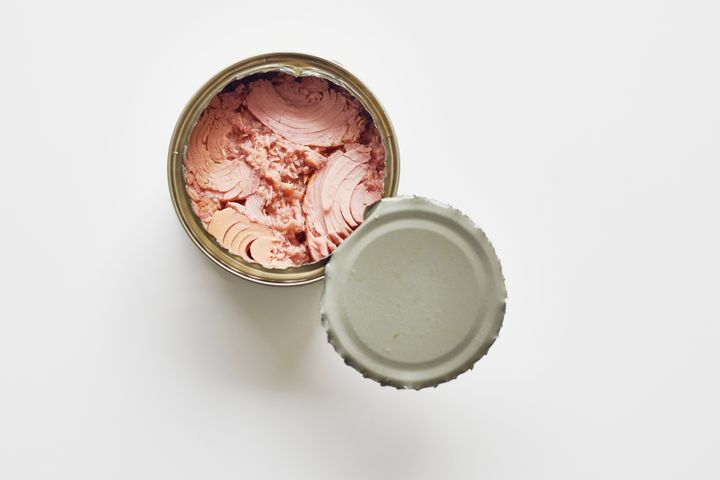 Opened can of Tuna fish against a plain white background.