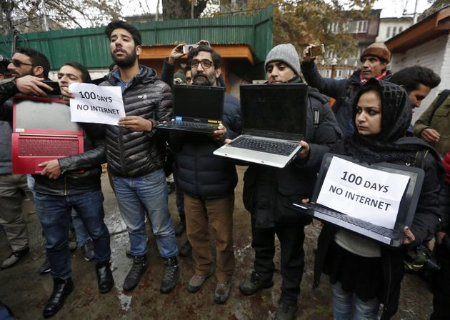 Kashmiri journalists display laptops and placards during a protest demanding restoration of internet...