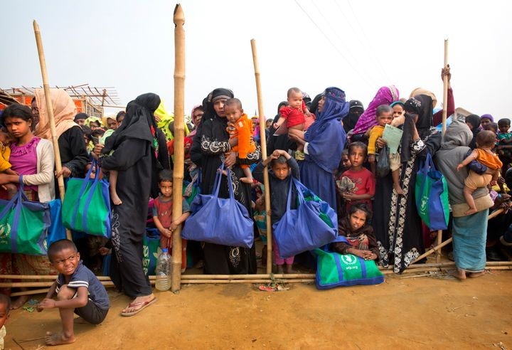 Rohingya Muslim women with their children stand in a queue outside a food distribution center at Balukhali refugee camp in Ba