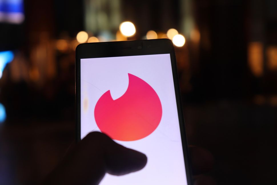 Tinder Logo can be seen on a Mobile Phone in New Delhi, India, on 26 July 2018. Tinder is a location-based social search mobile app that allows users to like or dislike other users, and allows users to chat if both parties swiped to the right. The app is often used as a hookup app (Photo by Nasir Kachroo/NurPhoto via Getty Images)