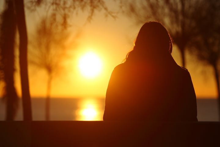 Back view portrait of a silhouette of a lonely woman watching sunset in winter