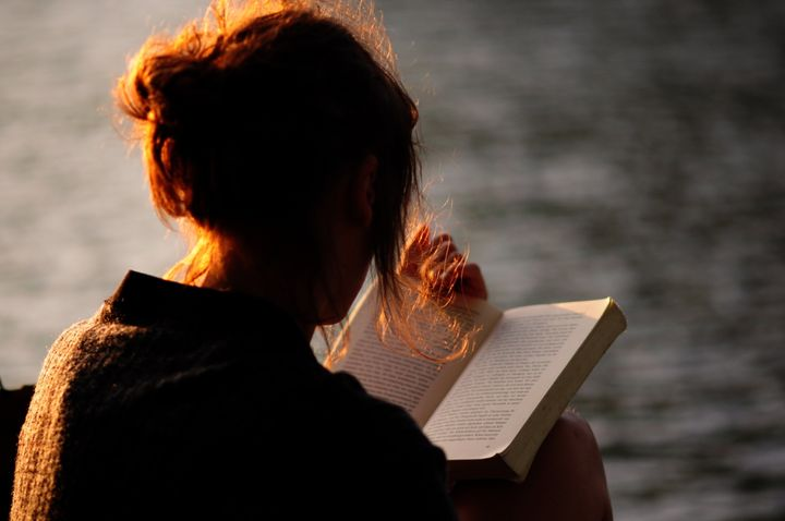 Rear View Of Woman Holding Book Against Lake