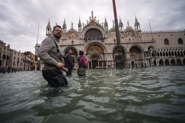 People are seen walking across the flooded St. Mark's Square on Friday in Venice. A massive flood defence...