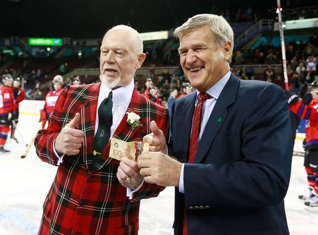 Don Cherry, left, and Bobby Orr hold up a $100 bill during a major junior top prospects hockey game in...