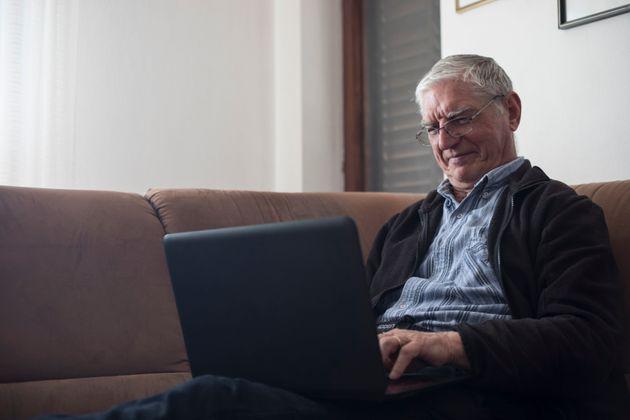 Smiling Senior Man Using Laptop While Relaxing in Living