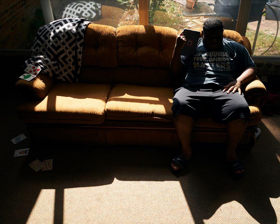 J.H. escucha música en su iPad en la terraza acristalada de su casa en Shreveport, Louisiana, el 25 de agosto