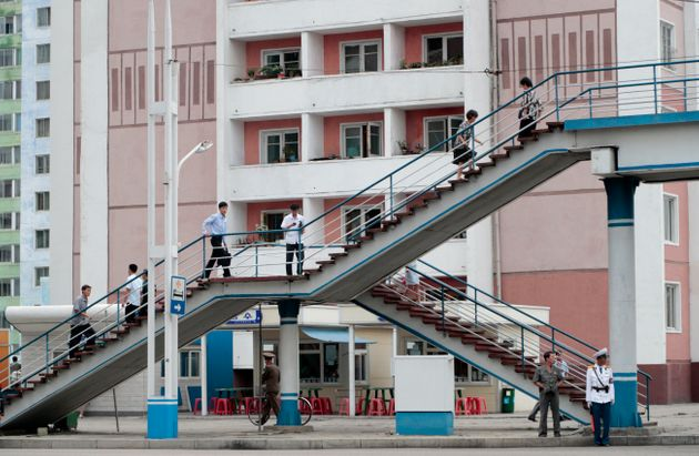 People walk on a pedestrian bridge as apartment buildings are seen in the background in Pyongyang, North...