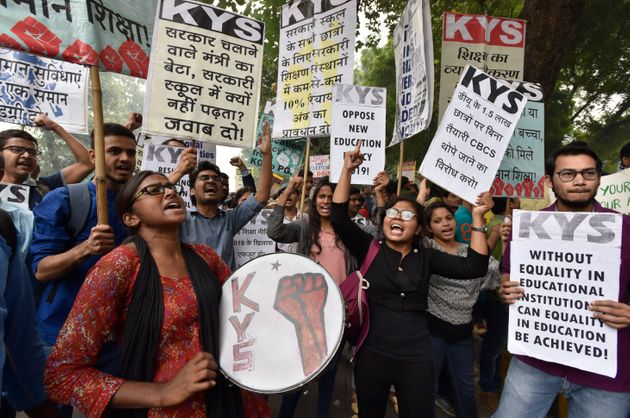 Teachers and students from various universities hold placards and shout slogans during a protest march...