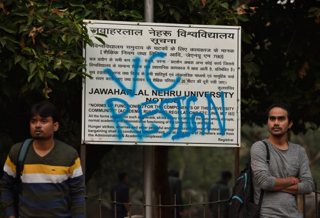 Students stand next to a notice board that has been sprayed with the slogan VC RESIGN, demanding the...