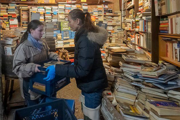 Volontari che salvano i volumi dall'acqua presso la Libreria Acqua Alta di