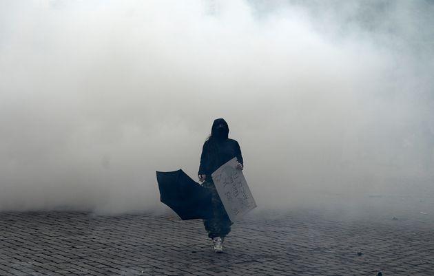 Une manifestante avec une pancarte et un parapluie dans un nuage de