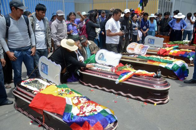 Relatives mourn by the coffins of supporters of Bolivian ex-President Evo Morales killed during clashes...